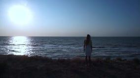 Przy falezą krawędź ziemia na żółtej trawie, stoi nieporuszonej dziewczyny w białej sukni z długimi blondynami, zbiory