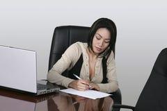 Przy jej biurowym biurkiem brunetki działanie Zdjęcia Stock