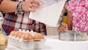Przy kuchnią córka odsiewa mąkę przez arfy zbiory wideo