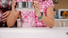 Przy kuchnią córka odsiewa mąkę przez arfy zdjęcie wideo
