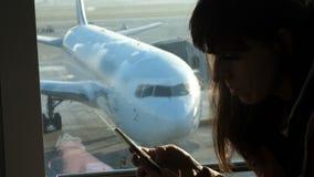 Przy lotniskiem w poczekalni przeciw tłu okno przegapia samoloty i pas startowego, siedzi a zbiory