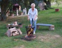 Przy ogniskiem w pożarniczym koszu młoda kobieta piec na grillu kiełbasy fotografia royalty free