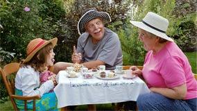 Przy ogrodowym herbacianym przyjęciem śmieszne twarze fotografia royalty free