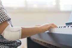 Przy rannymi rękami bawić się pianino azjatykcie chłopiec, Uczy się pianino Zdjęcia Stock