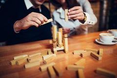 Przy sklep z kawą rękami na stole składającym intryguje Bawić się jenga na stole, drewniany tol, par sztuki Zdjęcie Royalty Free