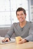 Przy stołem młodego człowieka szczęśliwy obsiadanie obraz stock