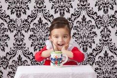 Przy stołem zdziwiona dziewczyna Fotografia Royalty Free