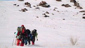 Przy stopą śnieżny wzgórze jest grupa doświadczeni arywiści, chcą wspinać się w górę wierzchołka i nad zdjęcie wideo