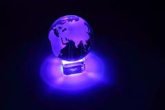 Przy szkło stojakiem szklana kula ziemska jest iluminuje Zdjęcie Royalty Free