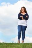 Przy trawą dziewczyna młodzi grubi stojaki Fotografia Stock