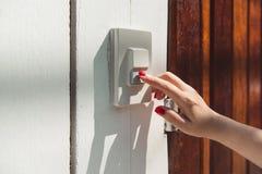 Przy wejściowym drzwi, kobiety ręka dzwoni przy drzwiowym dzwonem Zdjęcie Stock