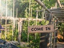 Przychodzący wewnątrz na drewnianym obwieszeniu podpisuje wewnątrz gospodarstwa rolnego lub ogródu dom Fotografia Royalty Free