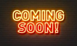 Przychodzić wkrótce neonowego znaka na ściana z cegieł tle zdjęcie royalty free