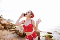 Przyczepia w górę dziewczyny opowiada na telefonie w czerwonym swimsuit Fotografia Royalty Free