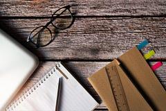 PrzyglÄ…da siÄ™ szkÅ'a i materiaÅ'y z laptopem na drewnianym stole zdjęcia stock