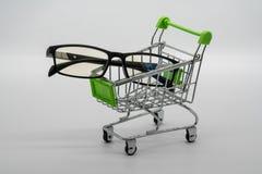 Przygląda się szkła lub odzież z wózek na zakupy na bielu obrazy stock