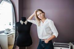 Przyglądająca ładna blond kobieta jest ubranym białą koszula stoi obok krawczyny atrapy Moda, krawczyny warsztat zdjęcia stock