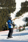 przyglądająca halna narciarka zatrzymujący ślad Fotografia Royalty Free