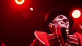 Przyglądający mężczyzn wykonawcy w kolorowym stroju tanczą na scenie z czerwonym oświetleniem zbiory wideo
