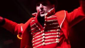 Przyglądający mężczyzn wykonawcy w kolorowym stroju tanczą na scenie z czerwonym oświetleniem zdjęcie wideo