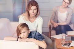 Przygnębiona chłopiec i jego matkujemy obsiadanie w biurze psycholog Obraz Stock