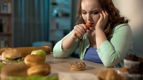 Przygnębiona dama je warzywa patrzeje słodkiego pączek i, odżywianie zdjęcia royalty free