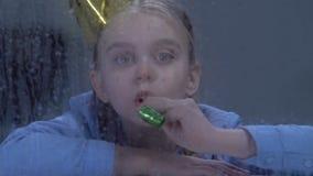Przygnębiona dziewczyna bawić się z partyjną dmuchawą za dżdżystym okno, znęcać się ofiary zdjęcie wideo