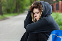 Przygnębiona dziewczyna w kapiszonu siedzącym puszku na drodze Fotografia Royalty Free