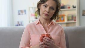 Przygnębiona kobieta pije kawę, patrzejący kamerę, przechodzi midlife kryzys zbiory