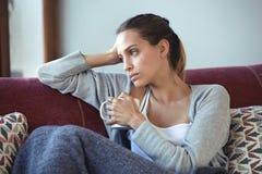 Przygnębiona młoda kobieta myśleć o jej problemach podczas gdy pijący kawę na kanapie w domu obrazy stock