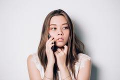Przygnębiona, nieszczęśliwa młoda kobieta używa jej mądrze telefon, fotografia royalty free