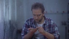 Przygnębione mężczyzny liczenia monety za dżdżystym okno, niscy dochody, ubóstwa pojęcie zbiory