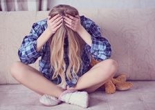 Przygnębionego nastolatka mienia siedząca głowa w rękach, następnie będzie misiem Zaakcentowana smutna młoda kobieta ma umysłoweg obraz royalty free
