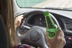 Przygnębiony żeński kierowca pije whisky od butelki dostaje szokujący jadący samochód Kobieta pije alkohol podczas gdy jadący sam fotografia stock
