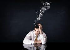 Przygnębiony biznesmen z dymienie głową Obrazy Royalty Free