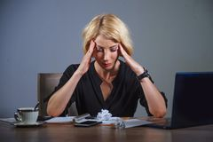 Przygnębiony biznesowej kobiety działanie przytłaczający przy biurem z laptopu uczuciem wyczerpywał cierpienie migrenę trzyma jej obraz stock