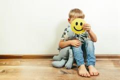 Przygnębiony chłopiec mienia uśmiech, udaje być świetny Twarz depresja fotografia royalty free