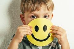 Przygnębiony chłopiec mienia uśmiech, udaje być świetny Twarz depresja obraz stock