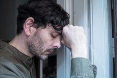 Przygnębiony mężczyzna przyglądający out okno w zdrowia psychicznego pojęciu w domu obraz stock
