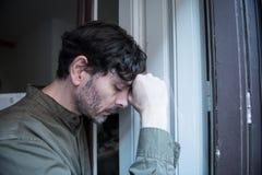 Przygnębiony mężczyzna przyglądający out okno w zdrowia psychicznego pojęciu w domu zdjęcie stock