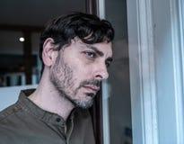 Przygnębiony mężczyzna przyglądający out okno w zdrowia psychicznego pojęciu w domu obrazy royalty free