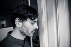 Przygnębiony mężczyzna przyglądający out okno w zdrowia psychicznego pojęciu w domu zdjęcie royalty free
