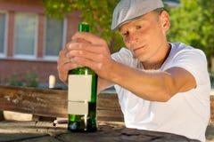 Przygnębiony mężczyzna trzyma butelkę napój zdjęcia royalty free
