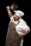 Przygnębiony młody szef kuchni smaży nieckę w kapeluszu i fartucha miotaniu Fotografia Stock