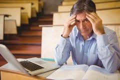 Przygnębiony profesora obsiadanie z notatkami i laptopem obrazy stock
