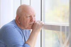 Przygnębiony starszy mężczyzna blisko okno zdjęcia royalty free