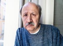 Przygnębiony stary człowiek patrzeje przez nadokiennego czuciowego samotnego i nieszczęśliwego cierpienia od depresji zdjęcie stock