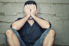 Przygnębiony młodego człowieka obsiadanie na podłoga i nakrycie jego stawia czoło Fotografia Stock