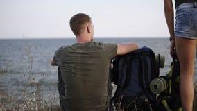Przygoda, podróż, turystyka, podwyżka i ludzie pojęć, Frontowy widok młody pary odprowadzenie z plecakami wzgórzem blisko zdjęcie wideo