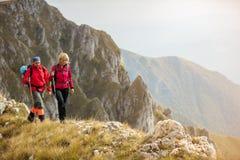 Przygoda, podróż, turystyka, podwyżka i ludzie pojęć, - uśmiechnięty pary odprowadzenie z plecakami outdoors obrazy stock